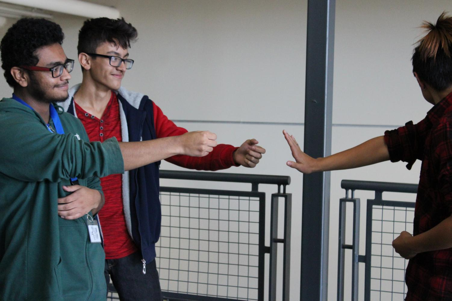 Students act out a scene of bullying in a school setting.