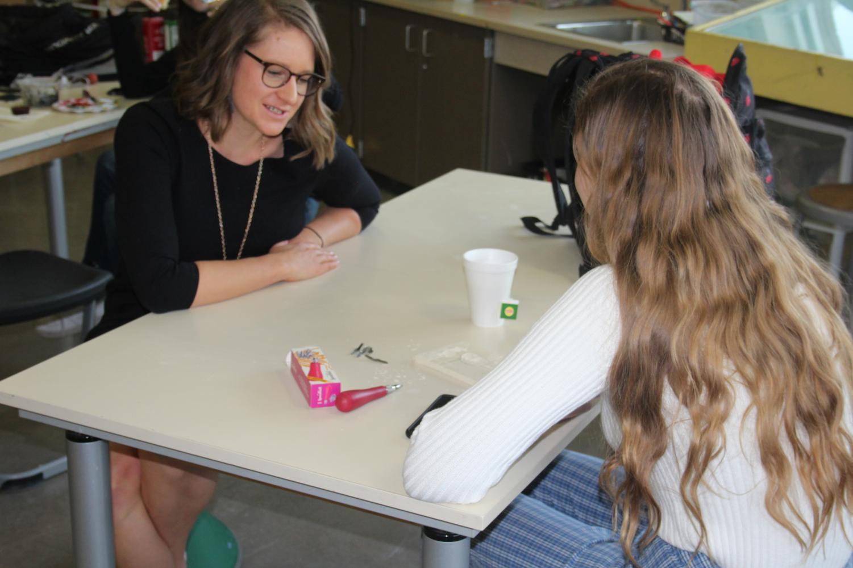 Teacher Emily Ancona aids a student in AP Art class