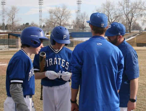 Coach Kyle Brink gives a few last minute pointers before the 3rd inning at bat.