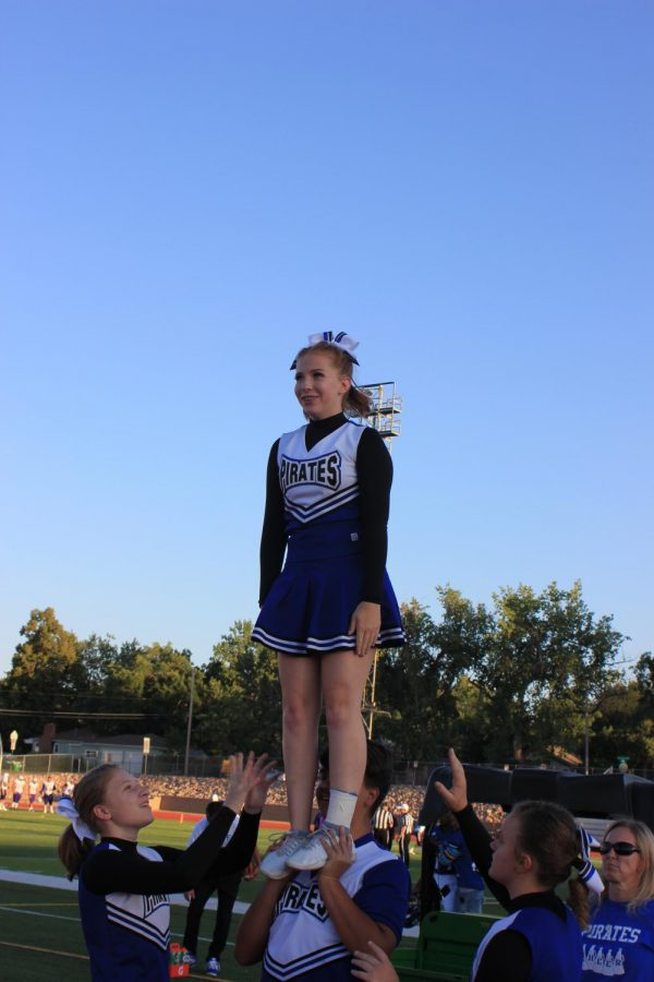 Emma Heidrick (9) stands on top of a pyramid. Cheerleaders consider themselves athletes but many struggle with including them. They say it is physical and involves a lot of practice.