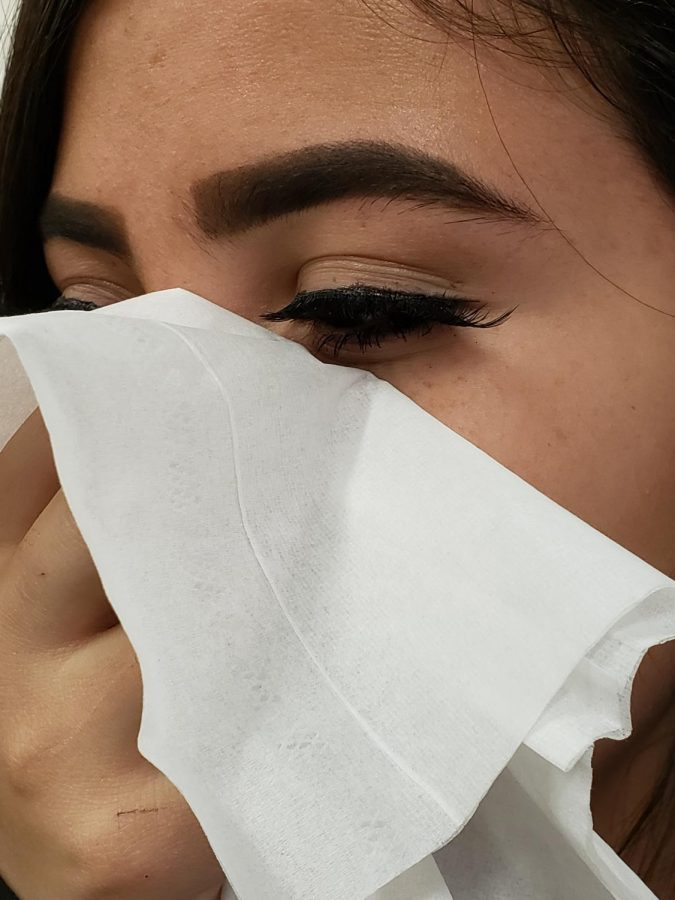 An EHS student uses a tissue to block a cough.