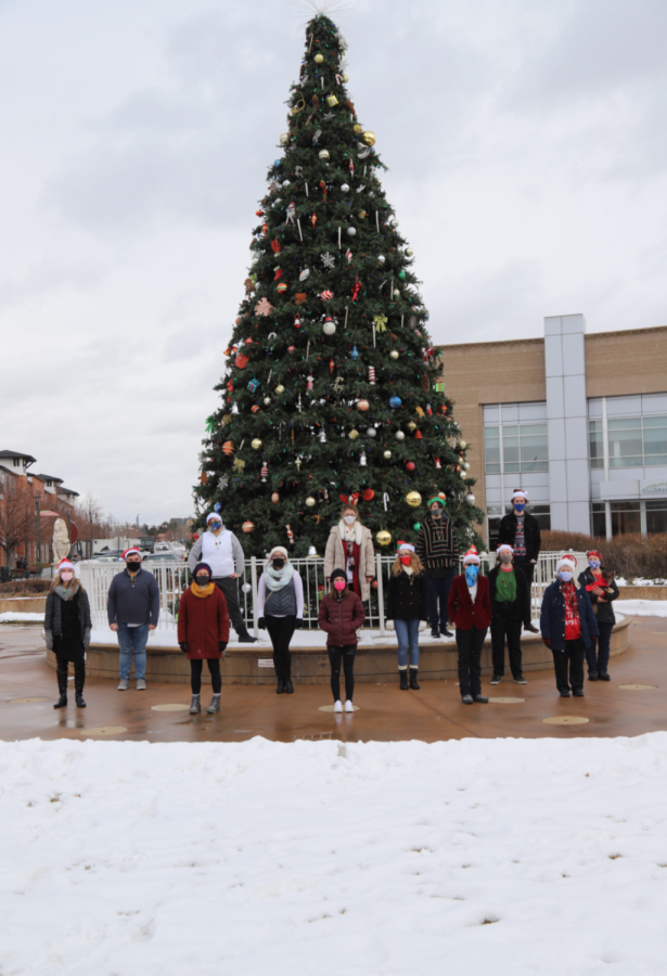 Carol of the bells Choir stands in front of the Englewood holiday tree.
